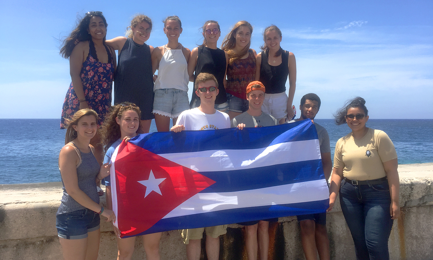 A group of 13 HWS students studied abroad to Havana, Cuba for a three week trip this summer to learn about Cuban history and culture. Here, the group poses with the Cuban flag on the Malecón in Vedado.
