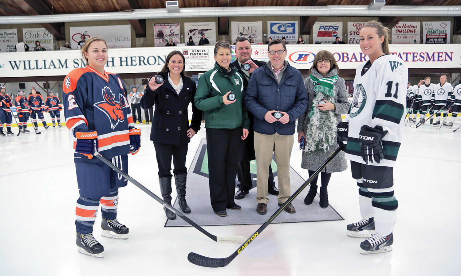 Utica forward Kelsey Dowdall, ECAC Associate Vice President for Leagues & Affiliates Katie Boldvich, William Smith Athletics Director Deb Steward, Geneva City Manager Matt Horn, President Emeritus Mark D. Gearan L.H.D. '17, Former Board Chair Maureen Collins Zupan '72, P'09 and Krista Federow '18 gather for the puck drop before the inaugural Heron home game.