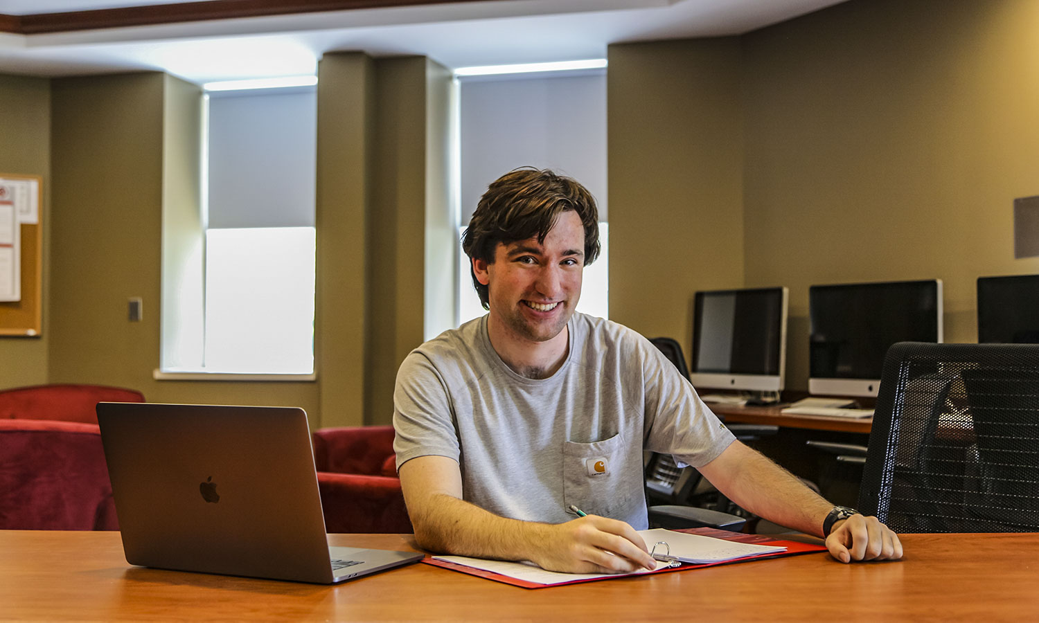 """Hugh Nick Mckenny '20 MAT '21, a Mathematics and Cognative Linguistics double major, sits in his favorite study spot, the basement of Merritt Hall. """"The friendliness and availability of the Education Department who are always willing to share their knowledge and offer guidance makes it my favorite place."""" Nick is on campus doing summer mathematics research with Professor Paul Kehle."""