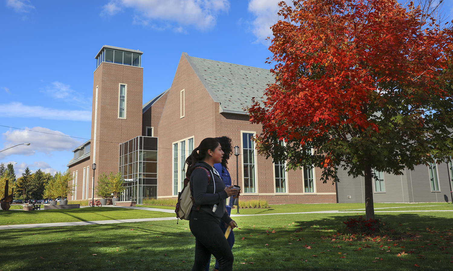 Students walk in front of the Gearan Center for the Performing Arts on a crisp fall day.