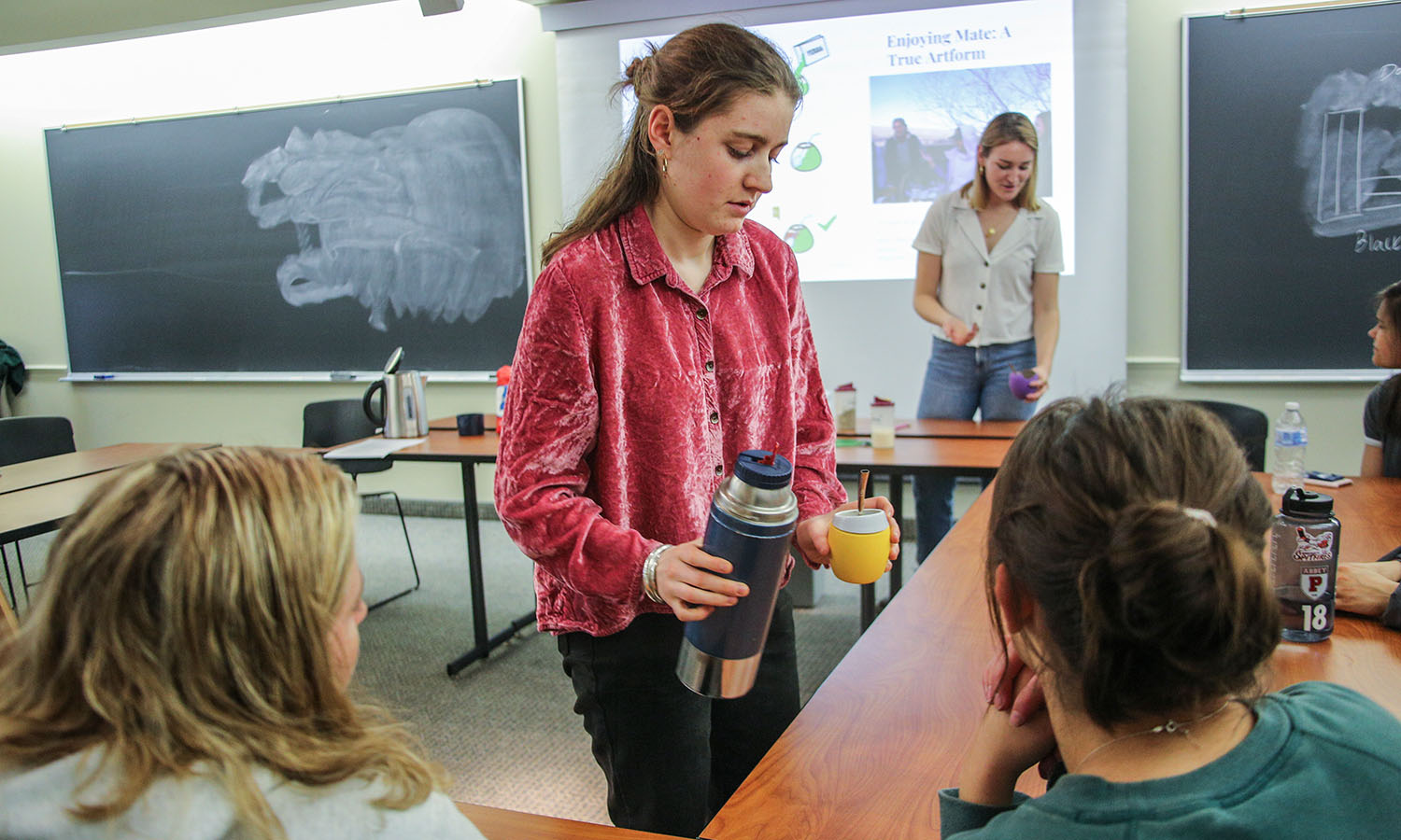 Audrey Platt '21 and Katherine Howard '19 give a presentation on Argentinian mate tea during the Global Cafe. Mate tea is a traditional South American infused drink.