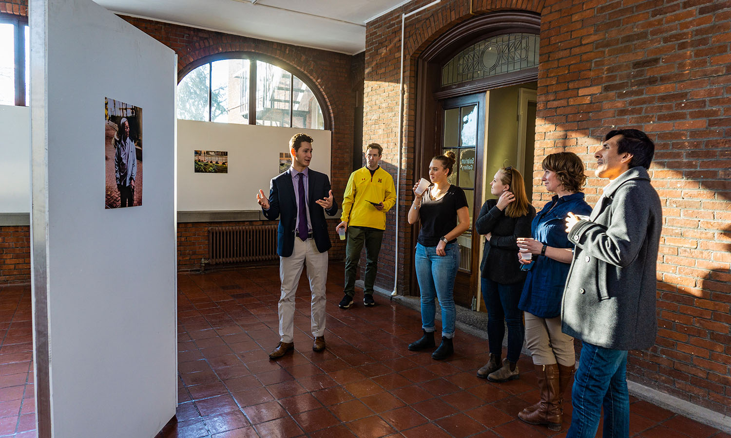 Jonah Salita '19 hosts a Global Cafe in the Solarium Gallery at Houghton House, showcasing his photographs of Fu Tei elders he took while studying abroad in Hong Kong.