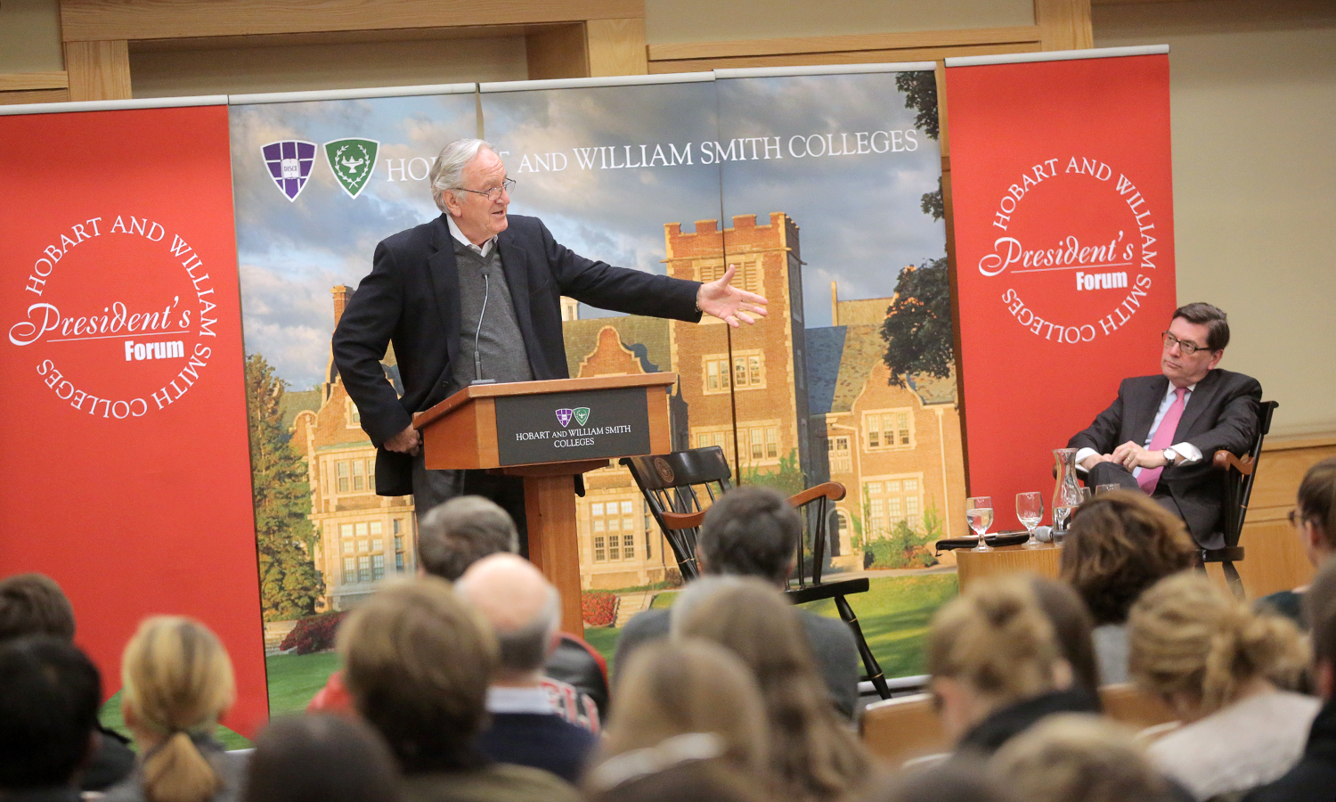"""President Mark D. Gearan looks on as Retired Senator Tom Harkin (D-Iowa) delivers his lecture titled, âLooking Forward: The ADA, Election, and You"""" as part of the President's Forum in the Vandervort Room of the Scandling Campus Center."""