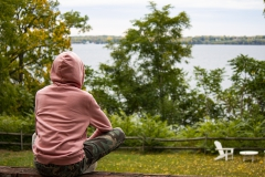 With a view of Seneca Lake, Kevin Lima '23 meditates alone in the Meditation House backyard.
