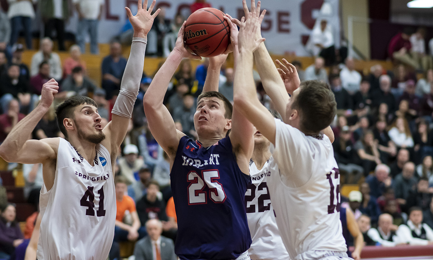 Jackson Meshanic '22 gets a shot off against three defenders. More than 1,500 Springfield College fans ringed the court during an intense second round of the NCAA tournament.