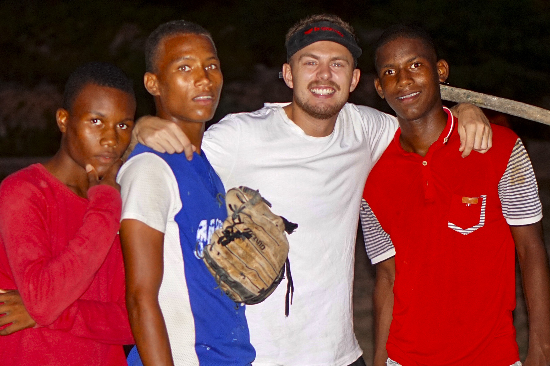 Carl Weiss '17 serves in the Dominican Republic. In the photo above, Weiss plays baseball with local youth.