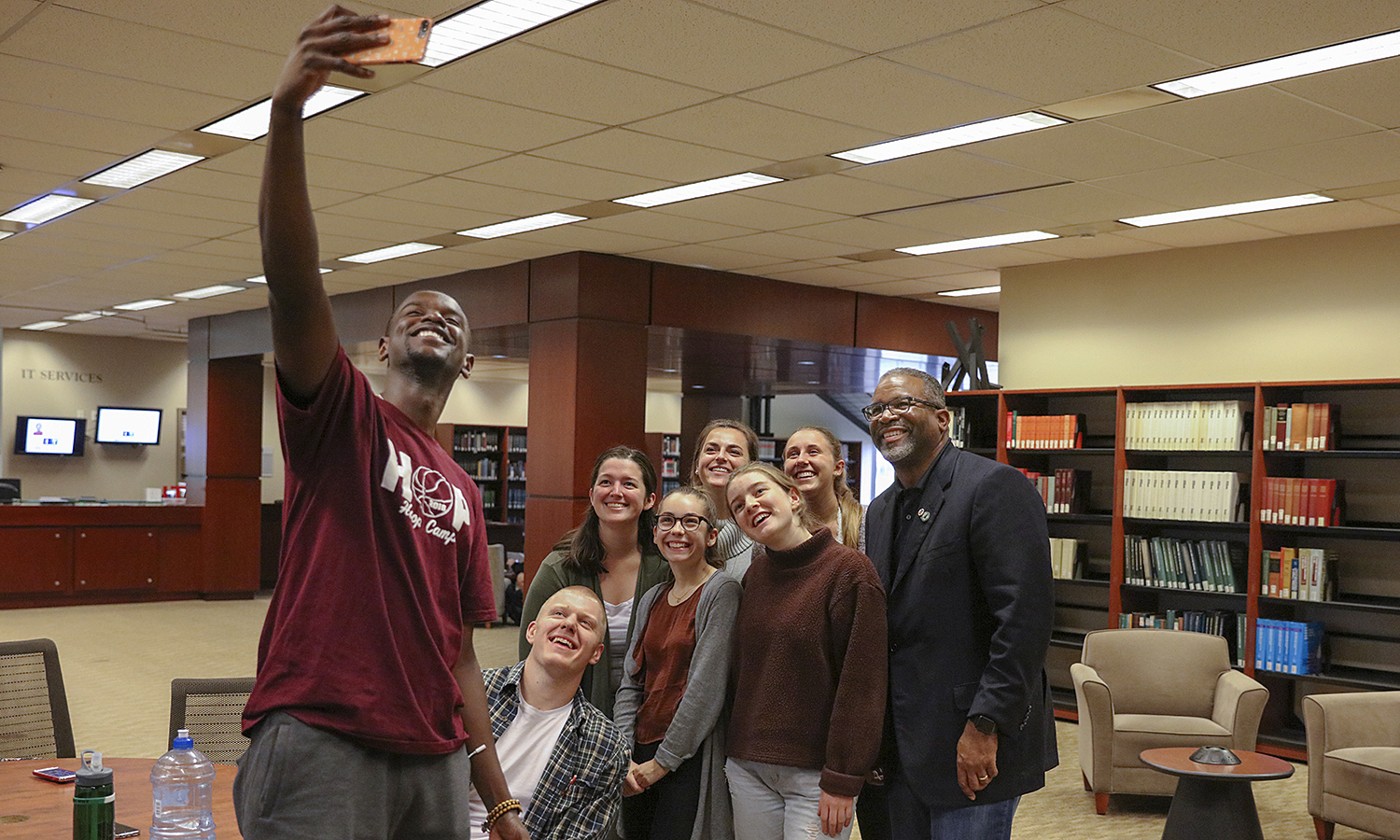 """Edens Fleurizard '20 snaps a """"groupie"""" with fellow students and President Gregory J. Vincent '83 in the Warren Hunting Smith Library."""