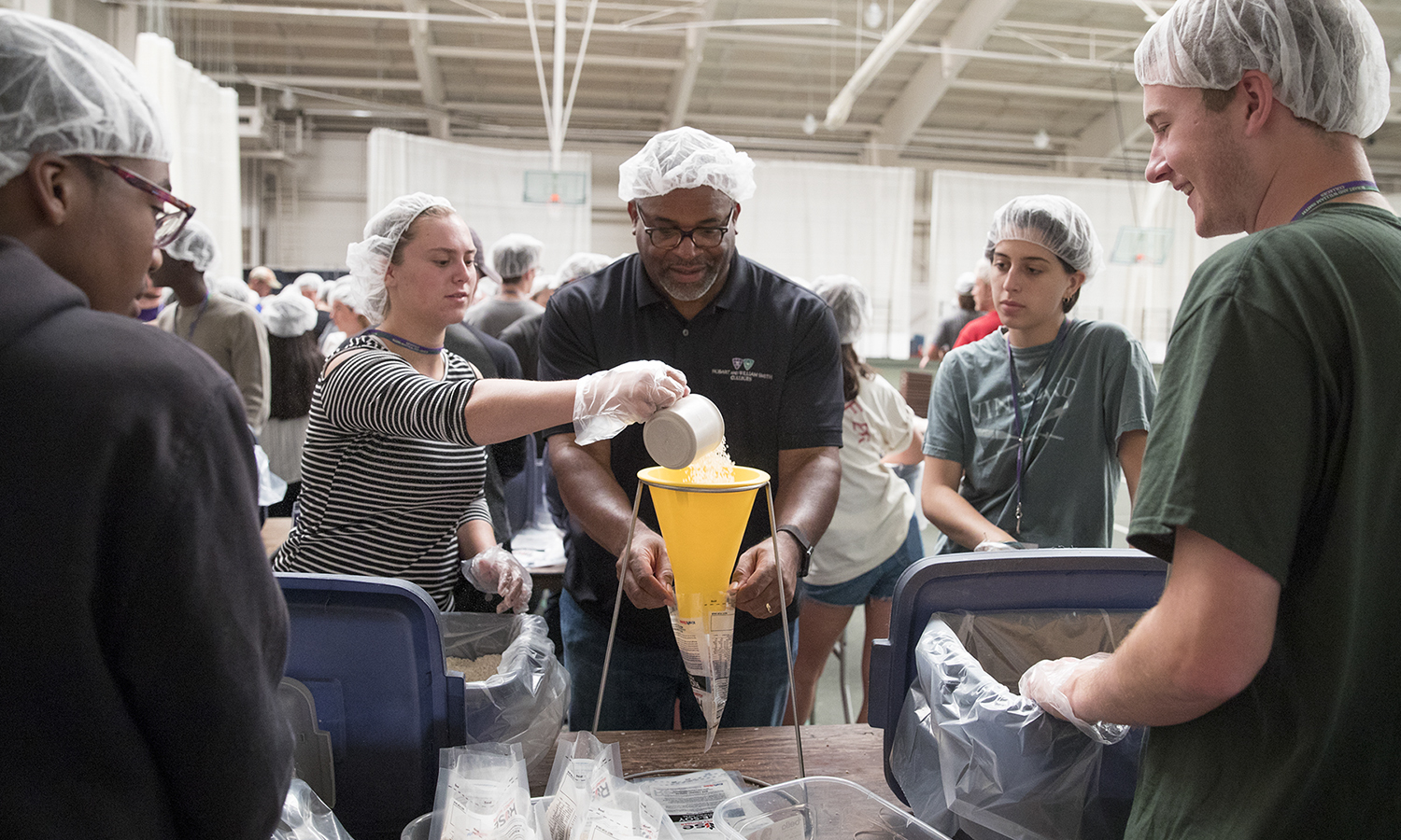 Maddie Ferguson '21 (right) looks on as Emma Ibbotson '21 helps President Gregory J. VIncent '83 package a meal for Rise Against Hunger in the Robert A. Bristol '31 Field House.