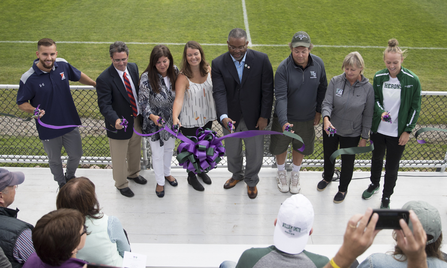 Adrian Colmenares '18, Hobart Soccer Head Coach Sean Griffin, Anne DeLaney, Emma Carver, President Gregory J. Vincent '83, Trustee Chip Carver '81, William Smith Soccer Head Coach Aliceann Wilber P'12 and Evie Manning '18 cut the ribbon on the newly constructed Carver-DeLaney Family Press Box at the John H. Cozzens Jr.'41 Memorial Field.
