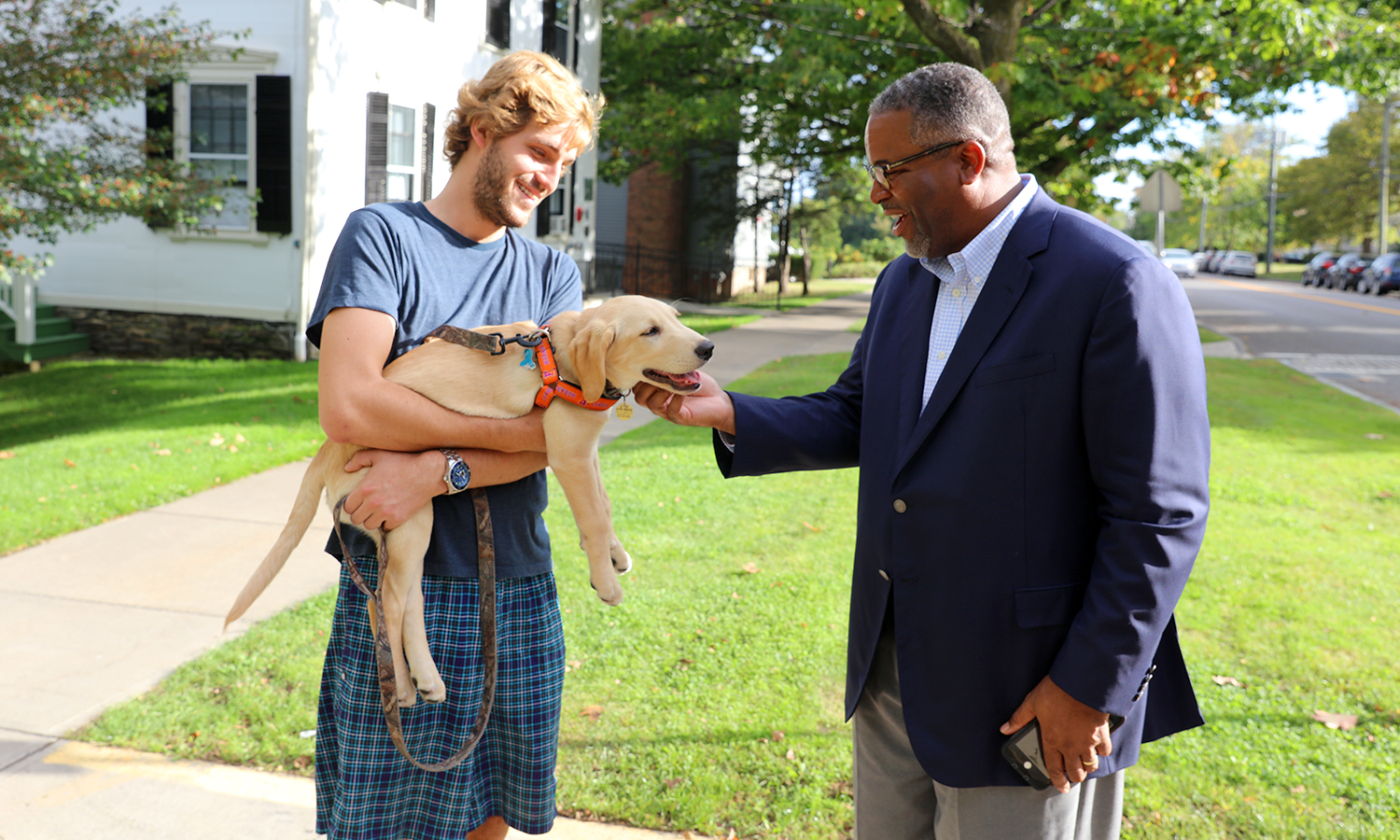 "Justin Podlesak '19 and ""Chapo"" greet President Gregory J. Vincent '83 outside the Thomas Poole Family Admissions Center."