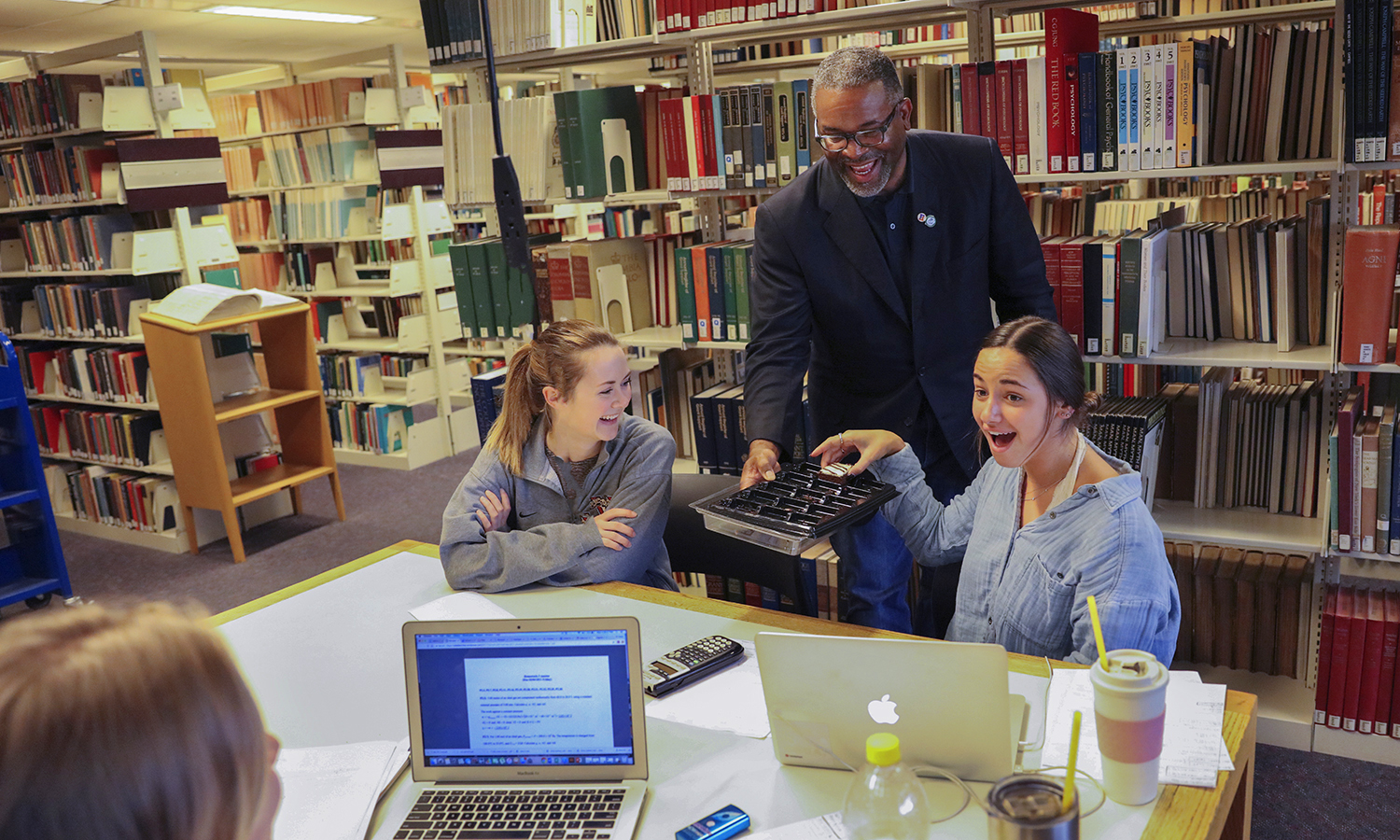 President Gregory J. Vincent '83 passes out snacks to Julia Raleigh '18 (left) and Sydney Smilen '18 in the Warren Hunting Smith Library.