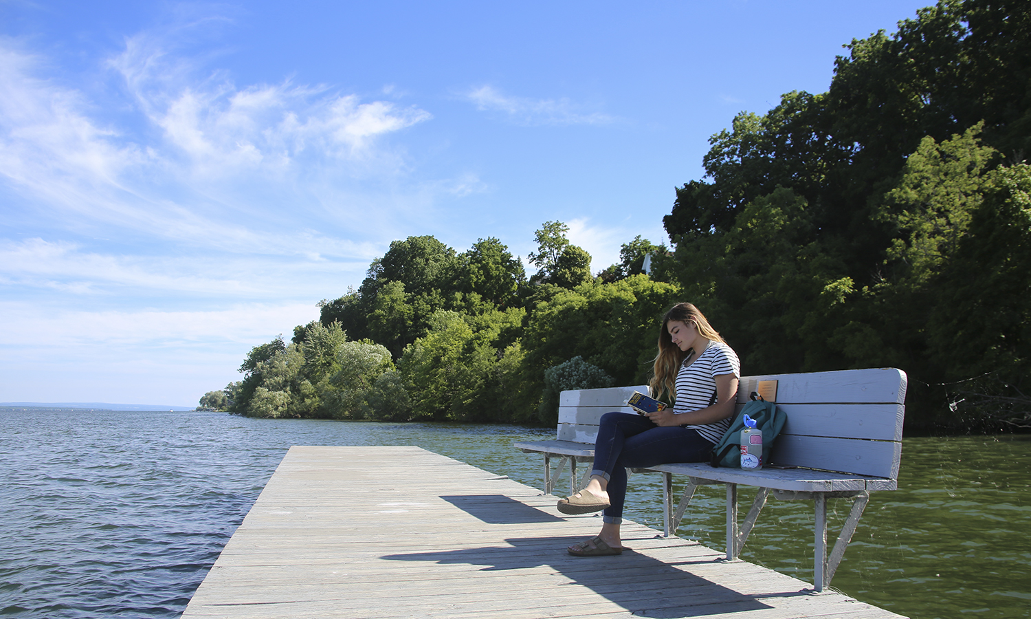 CCESL summer intern, Edie Falk '21, is shown sitting in her favourite place to read and relax on campus, the benches by the boathouse. She likes how calm the boathouse is, giving her the opportunity to read her favourite summer book, The Great Gatsby by F. Scott Fitzgerald.