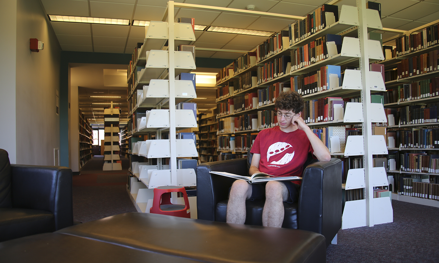 "Sitting in the same seat he selected during freshman orientation, senior Austin Jennings reads ""Designing for the Theatre: A Memoir and a Portfolio"" by Jo Mielziner, his favourite book in the library. Austin in in Geneva over the summer as a Research Assistant to Dr. Chris Woodworth, Associate Professor of Theatre."