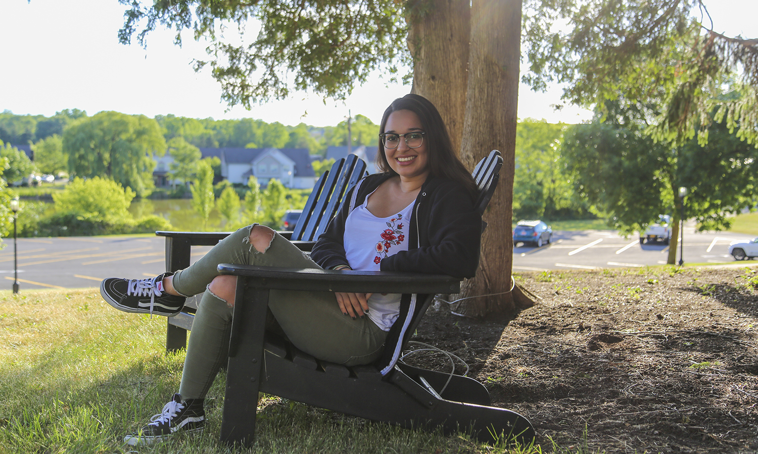 Kenza Kebdani '21 sits behind Comstock overlooking Odell's Pond. This is her favourite place on campus because it was the first spot she found where she could relax after a long day of classes and enjoy the view.