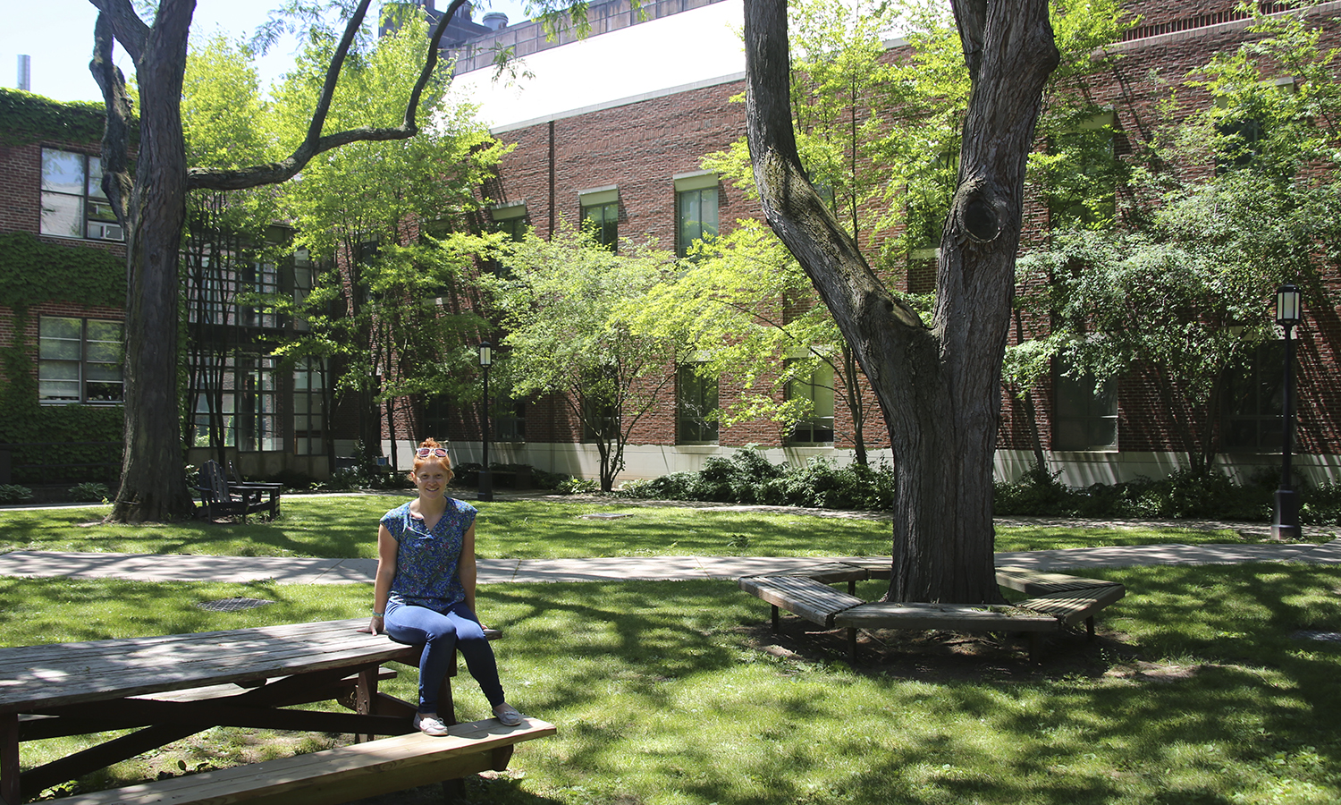 "Therese Mandracchia '19, a Biochemisty major, sits in the small quad in the middle of the sciences complex. This is her favourite place on campus because in the summer, ""it's shady and breezy."" Therese is at HWS over the summer reaserching milkweed genetics with Professor Straub in the Biology Department."