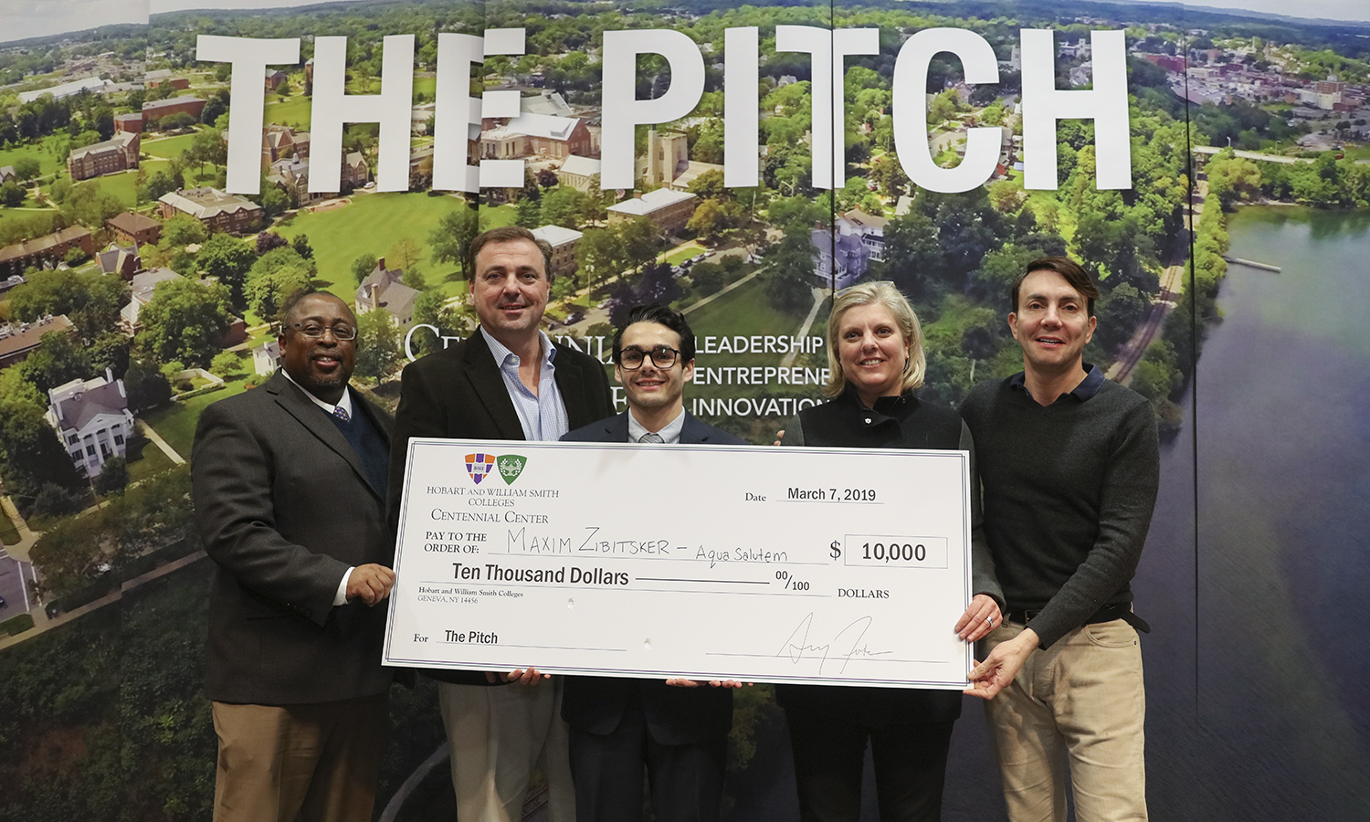 "The judges, including (left to right) HWS Trustee Michael Rawlins '80, P'16, principal user experience design architect for the Walt Disney Company; Philip Yawman '87, president at the Colley Group, Inc.; Caroline Ross Galdabini '89, head of marketing at Citi Private Bank; and Eric Cohler '81, interior designer, art historian and adjunct professor of architectural studies present Maxim Zibitsker '19 with a check for $10,000 to launch his company ""Aqua Salutem Technologies."""