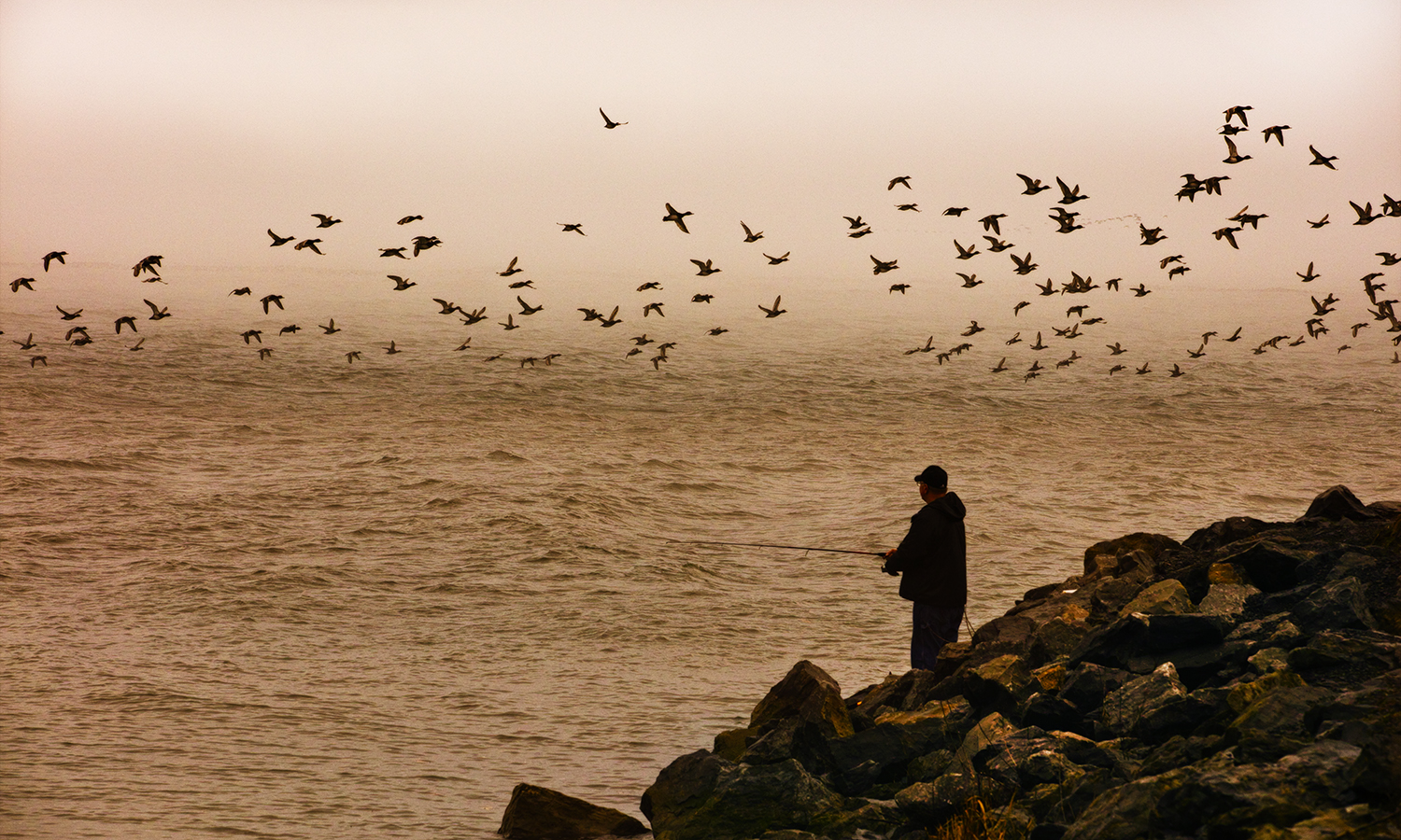 A lone fisherman stands on the Geneva Pier.