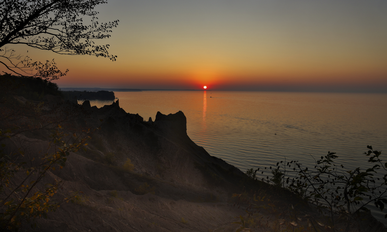 The sun sets over Lake Ontario at Chimney Bluffs State Park in Wolcott, N.Y.
