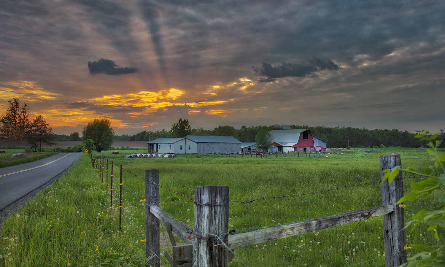 Light cracks through the clouds above a farm in Tyre, N.Y.