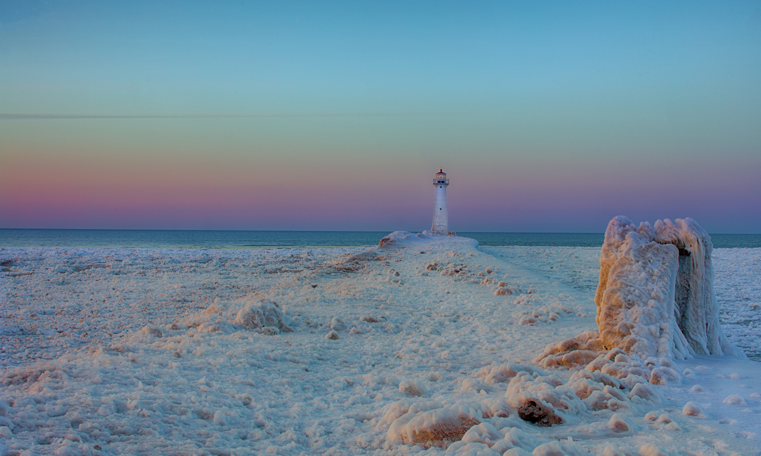 A band of color illuminates the sky above the icy waters of Lake Ontario in Sodus Point, N.Y.
