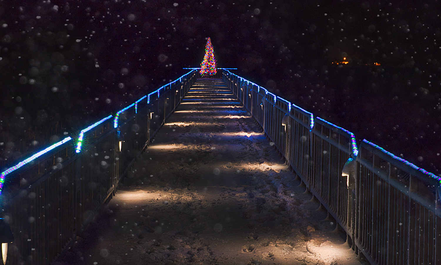 The Long Pier at the Geneva Lakefront glows with holiday lights on a snowy evening.