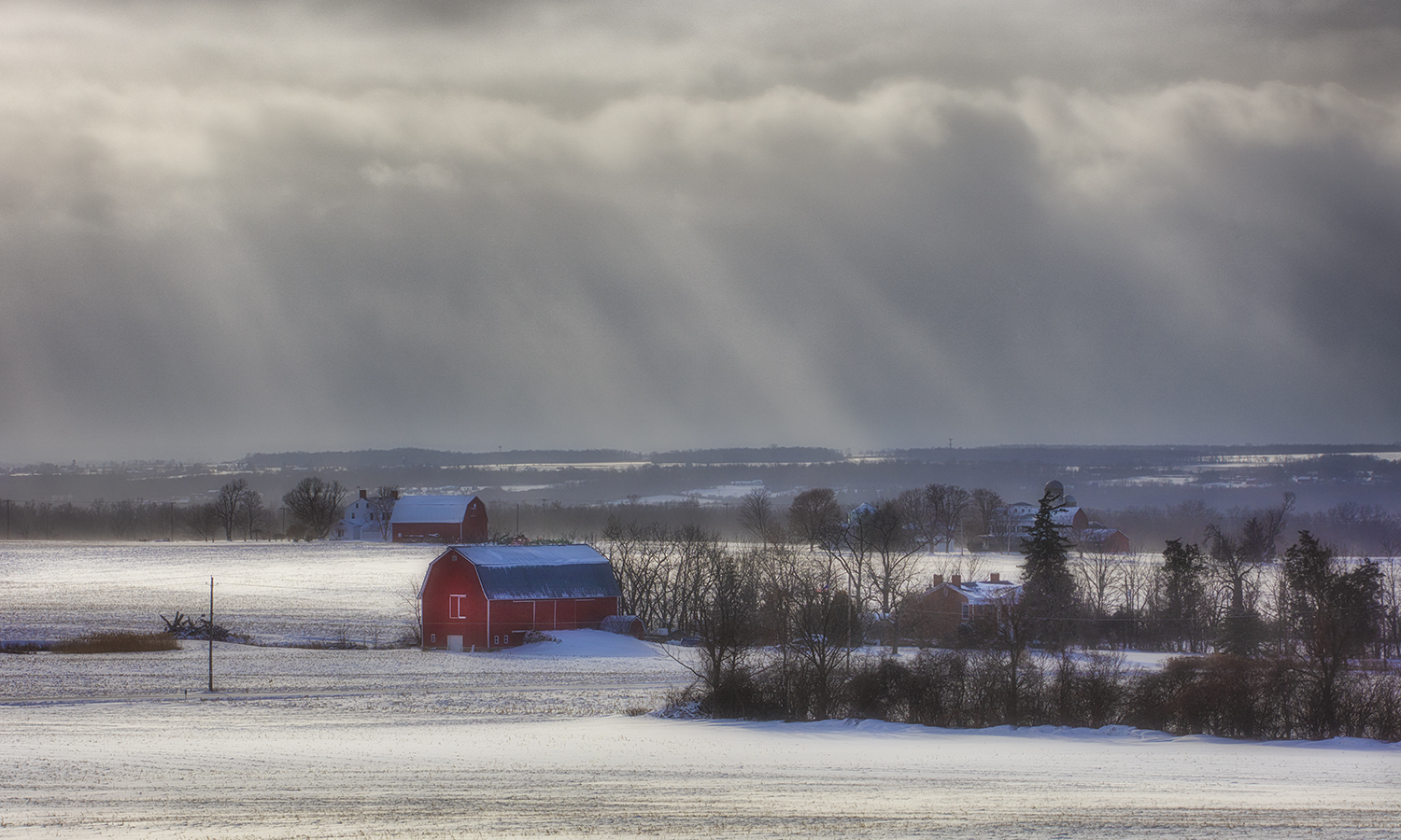 Snow moves across red barns and over open fields along Route 96A.