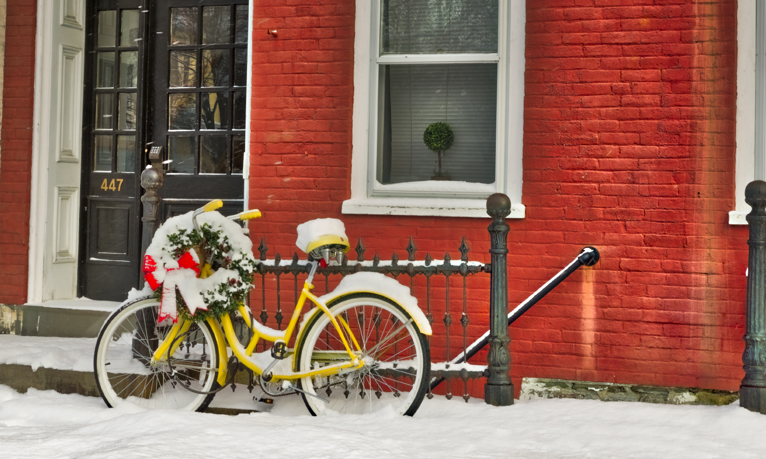 Snow covers a yellow bicycle on South Main Street.