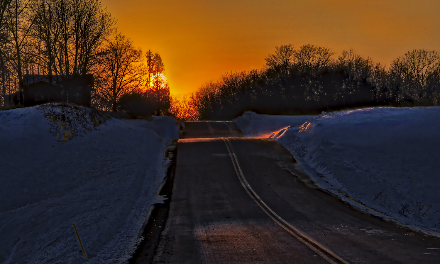 The sun creates a golden glow across a wintry country road in Tyre, N.Y.
