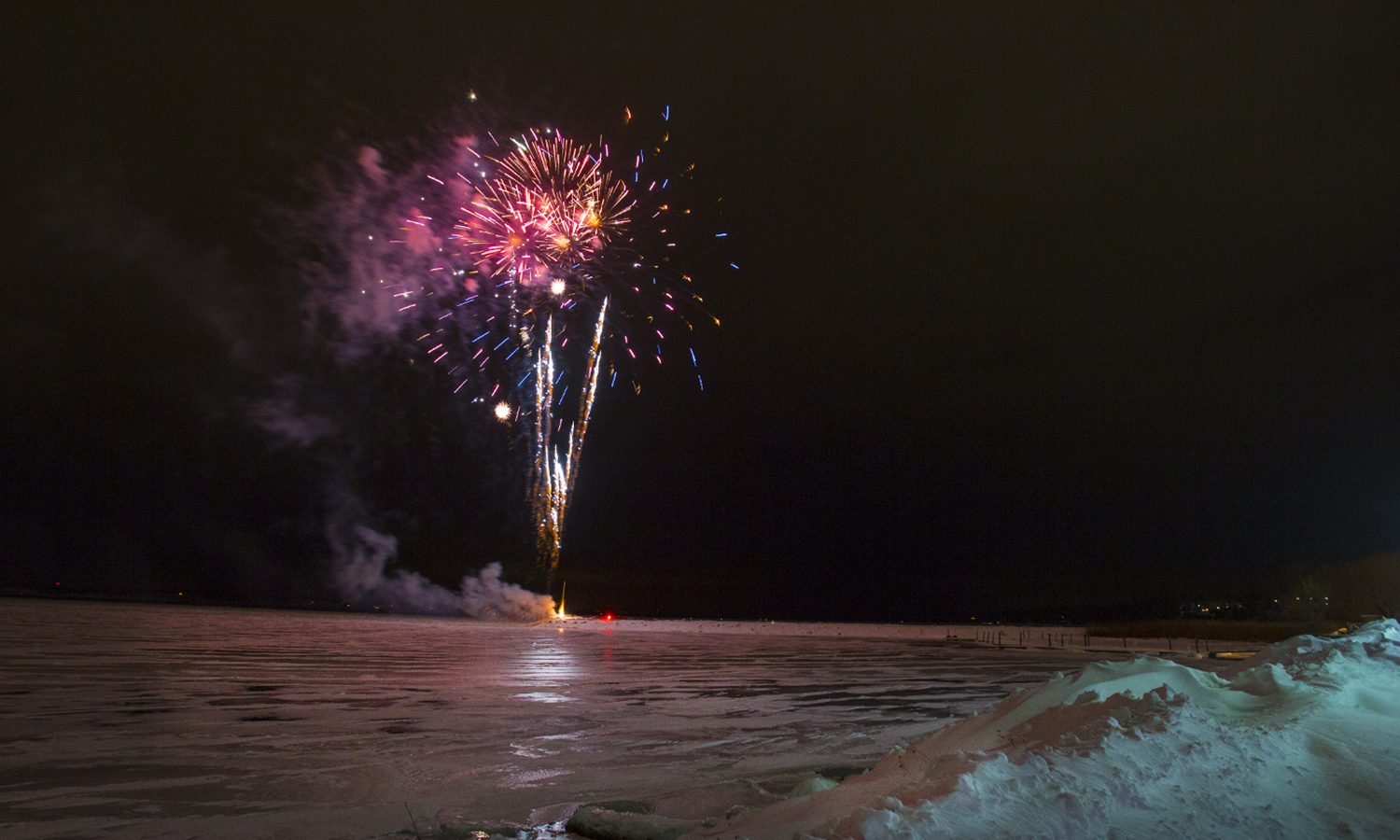 Fireworks burst in the air over Long Pier in Geneva during a winter celebration.