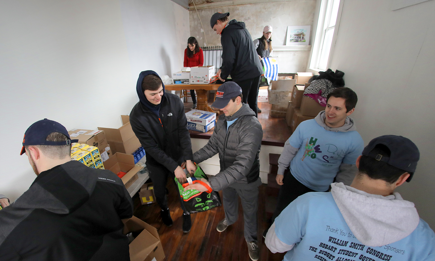 Students help Jackie Ausgustine (back, left), organizer for the Seneca7, prepare supplies for the upcoming race on April 29th in Geneva, N.Y.