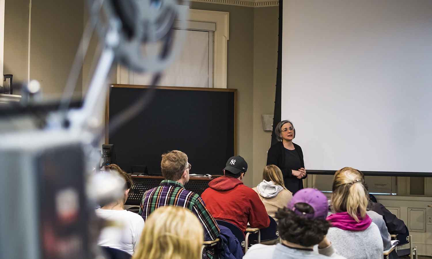 """Rochester based filmmaker Tara Merenda-Nelson explains the the mechanism of projected celluloid cinema and its unique physiological effect on human perception during her talk """"Cinema Biolgy"""" in Houghton House."""