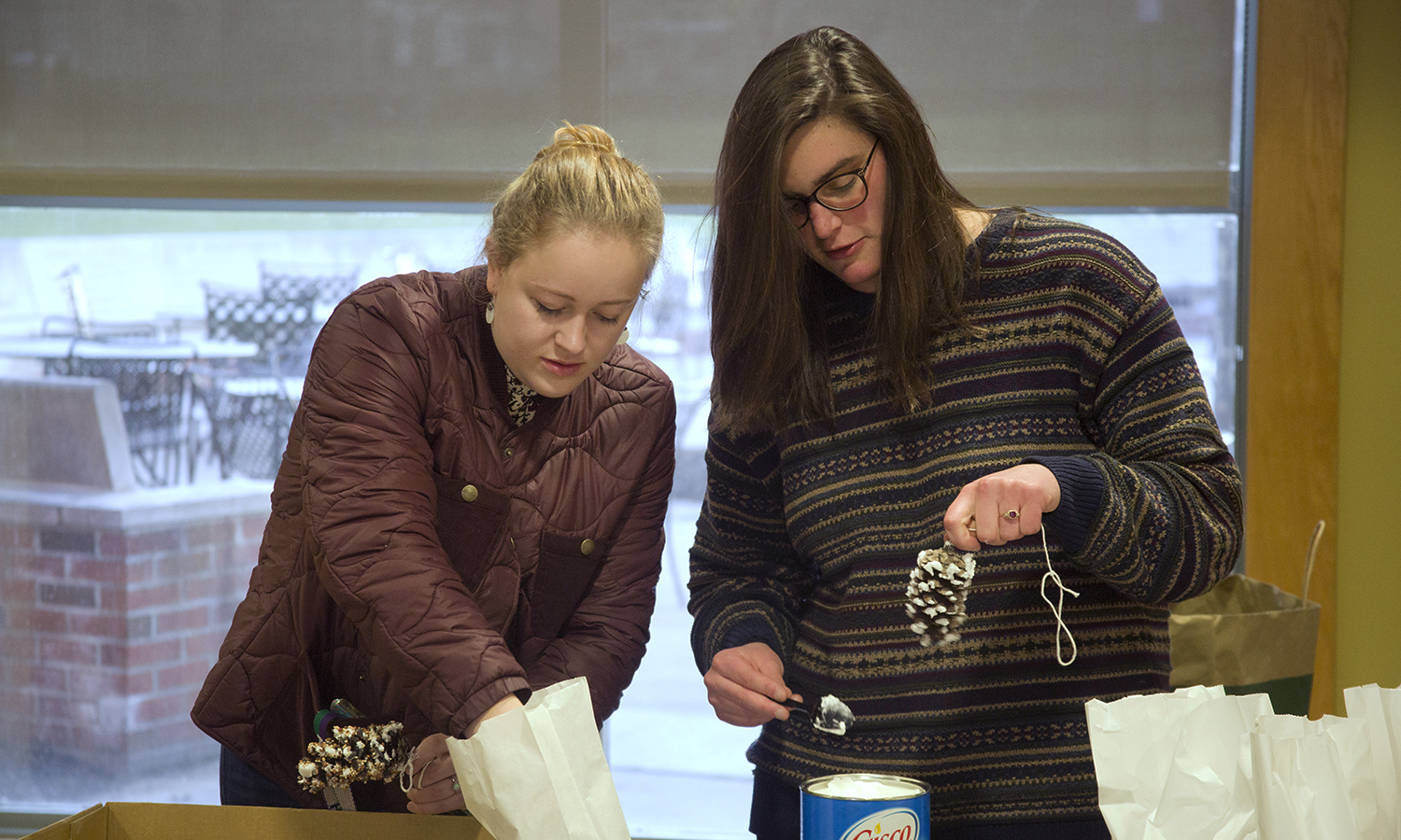 As part of Earth Week, Katie Burns '18 (left) and Rebecca Czajkowski '18 craft pinecone birdfeeders in Scandling Campus Center.