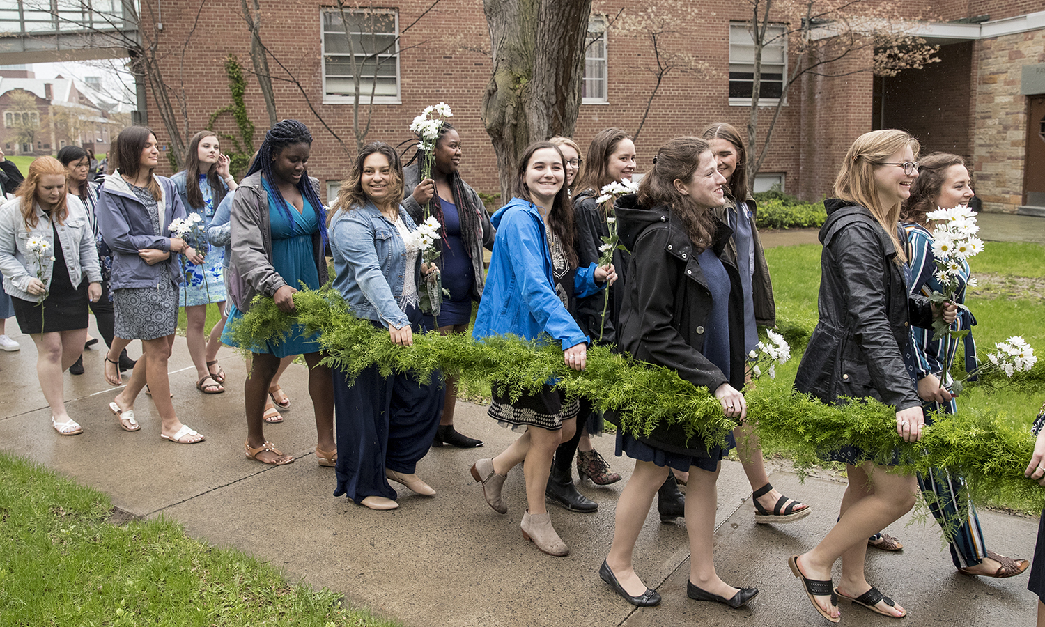 "William Smith seniors carry a laurel garland during the procession that kicks off Moving Up Day. The seniors pass the garland to juniors and all students ""moving up."""