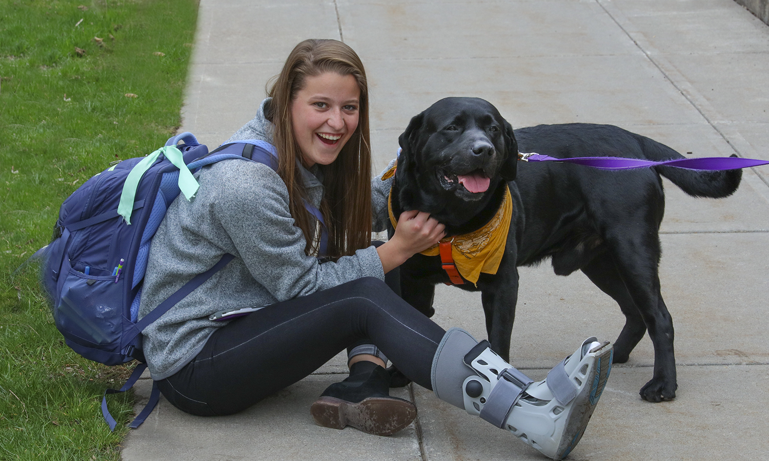 "Kate Foley '20 poses for a photo with Assistant Athletic Trainer Sara Siewerth's dog ""Jack""."