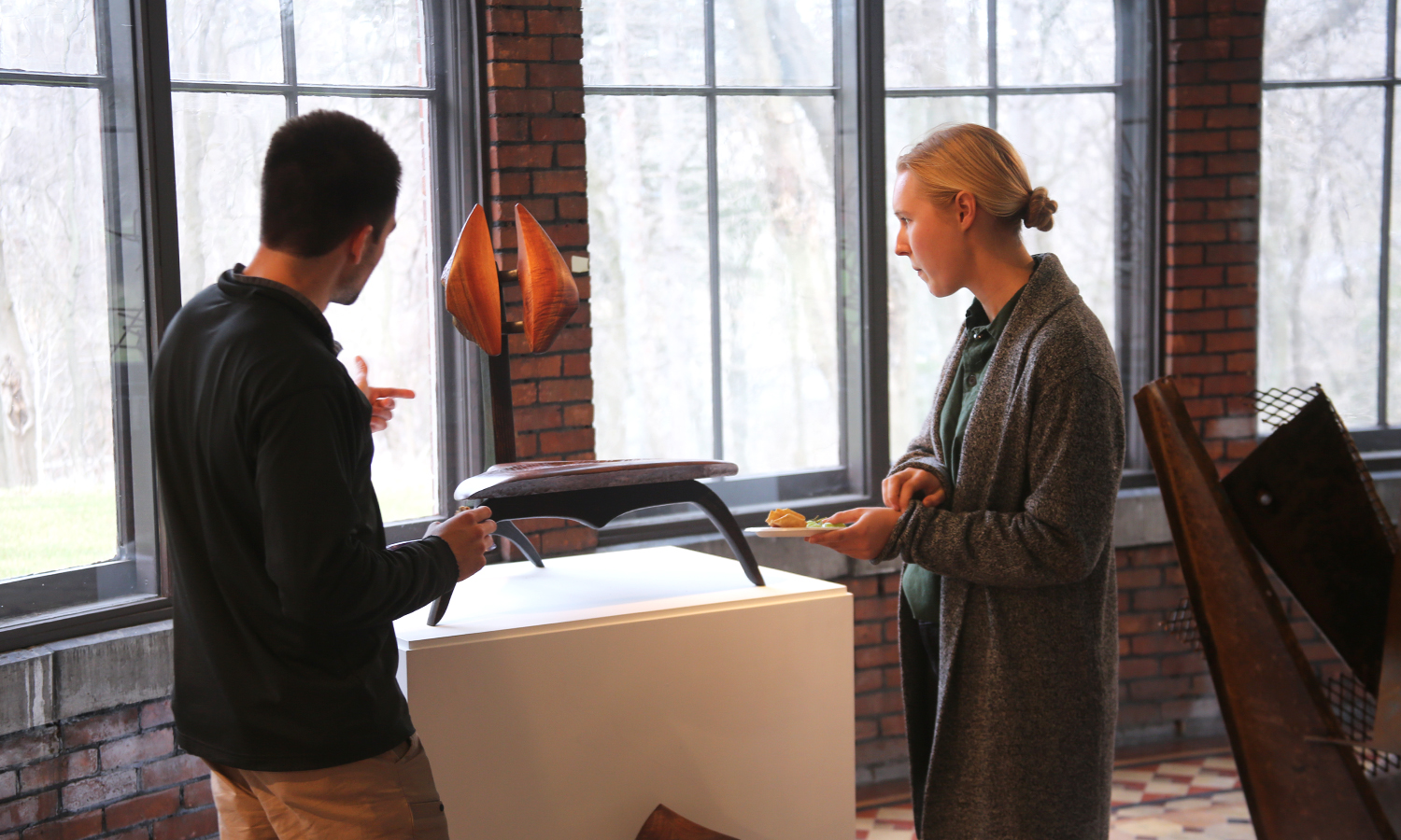 "Remington McGuire 'X and Aubrey Johnson 'X examine a piece during ""Student Art and Architecture: Studio Work from 2017-2018"" in the Davis Gallery at Houghton House."