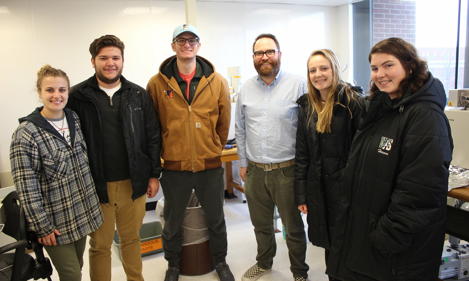 "Led by Associate Professor of Geoscience David Kendrick, students in ""Paleontology"" gather for a photo with assistant professor of earth sciences Christopher Junium (third from left) after reciving a tour of the Geobiology, Astrobiology, Paleoclimate and Paleoceanography (GAPP) Lab."