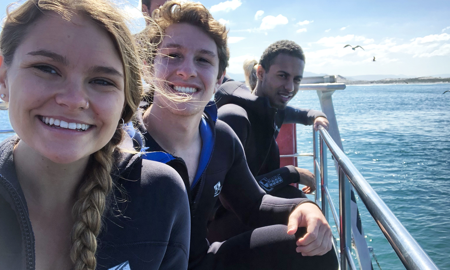 Dani Gosselin ('19), Dylan Morris ('19), and Donovan Hayden ('19) prepare to go shark cage diving while studying abroad in Gansbaii, South Africa