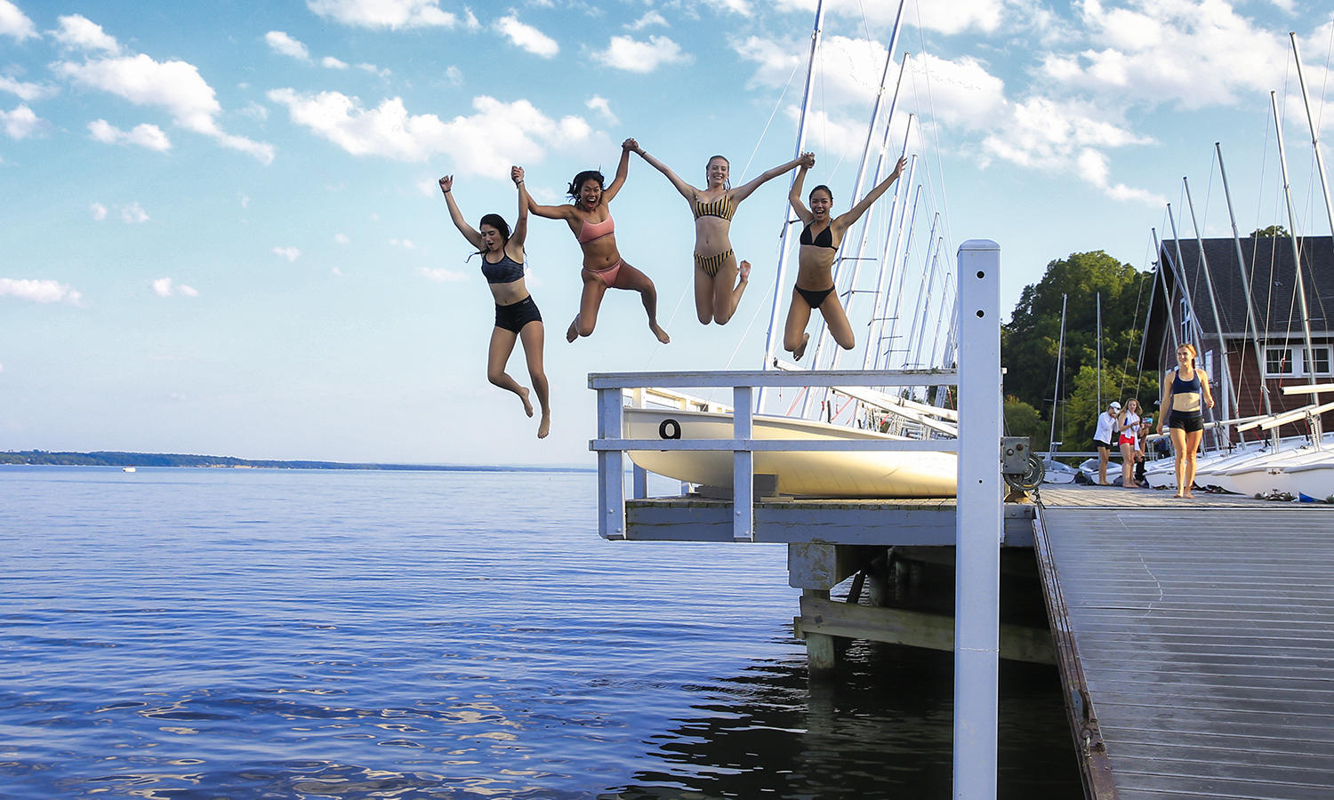 Members of the William Smith Cross Country jump into Seneca Lake.