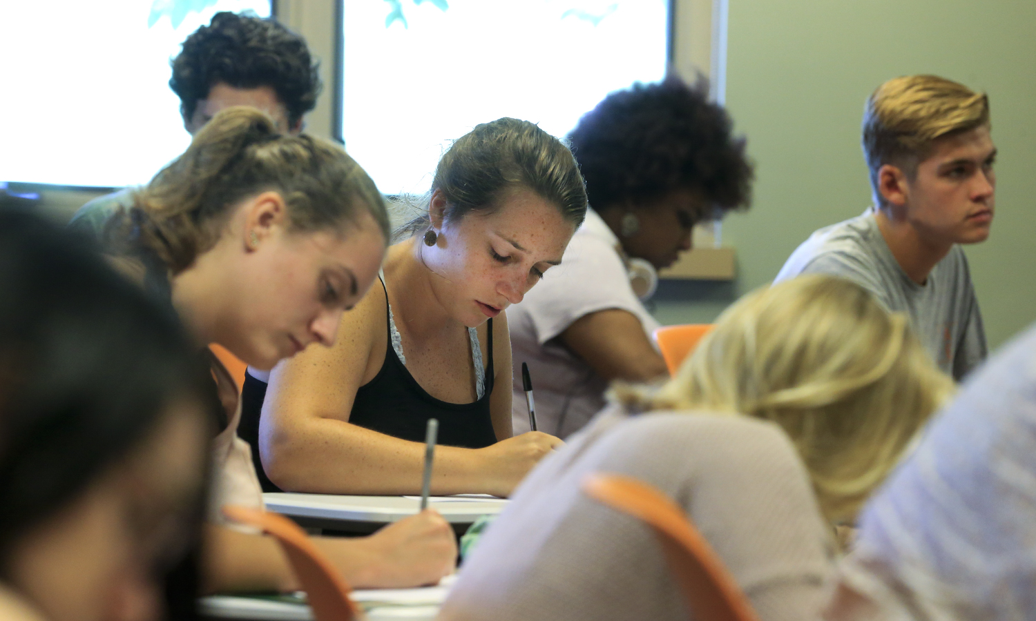 _______ and her classmates take notes during a class on Monday.