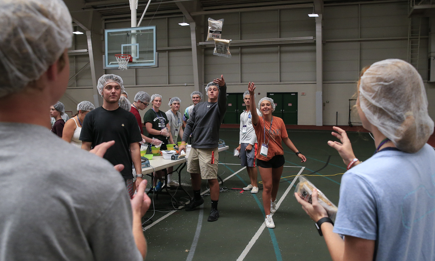 First-year students pass meal packages along an assembly line at Bristol Field House during the 2018 Day of Service.