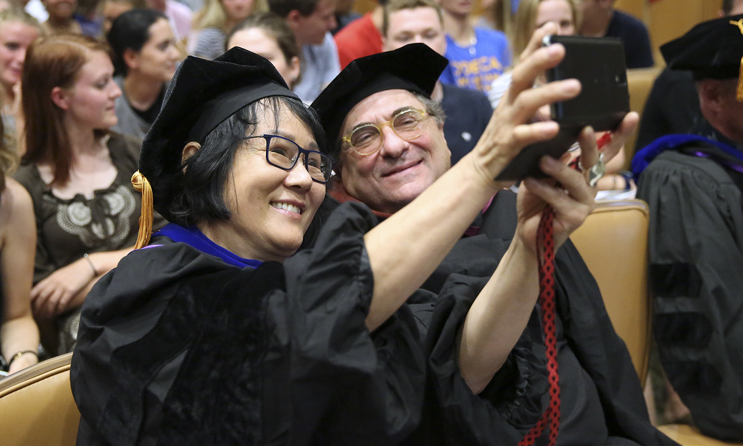 Professors of Art and Architecture Phillia Yi and  A.E. Ted Aub III take a selfie during Associate Professor of Media and Society Leah Shafer's remarks. Shafer asked the audience to take selfies in order to capture the present moment.