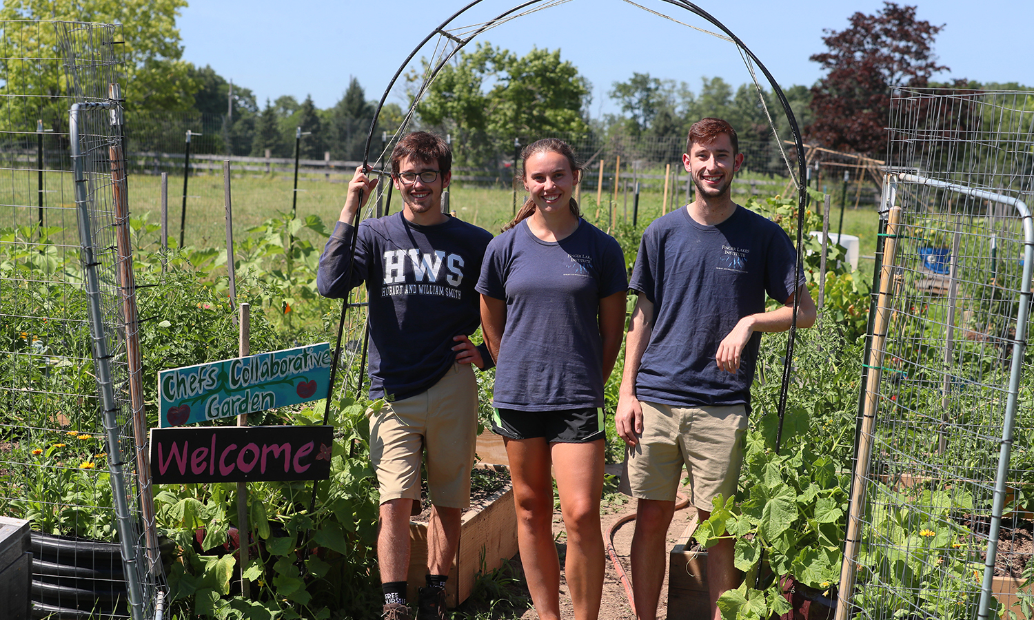 Fribolin Farm interns Sam Horner '21 and Eileen Rath '20 and Summer of Service intern Alexander Cottrell '20 pose at the entrance of the Chef's Collaborative Garden on HWS Fribolin Farm. The students were able to complete day-to-day tasks on the Farm through the Finger Lakes Institute.