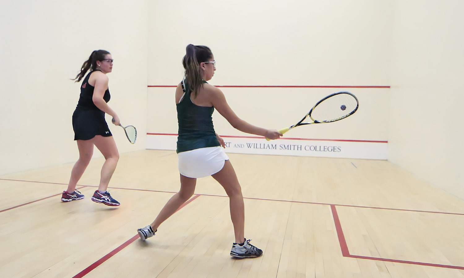 Joana Pacheco '21 hits a forehand during William Smith's squash match against Dickenson College.