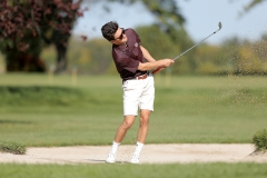 Peter Kapsimalis '19 hits a shot out of the bunker during a practice round at Clifton Springs Country Club.