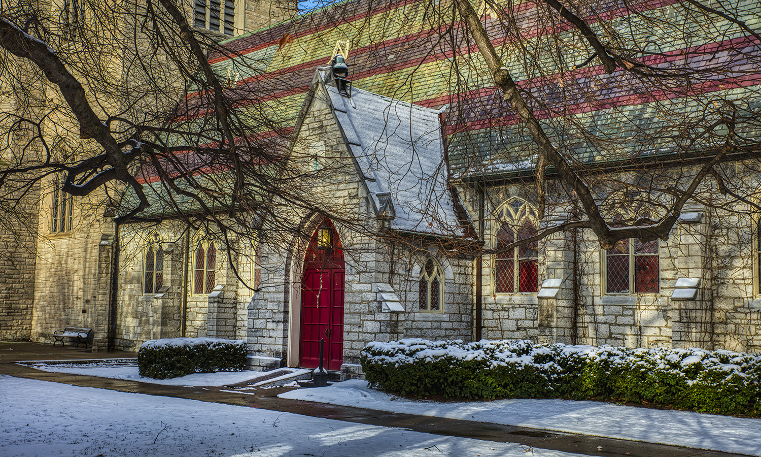 The red doors of the chapel illuminated by sunlight in December.