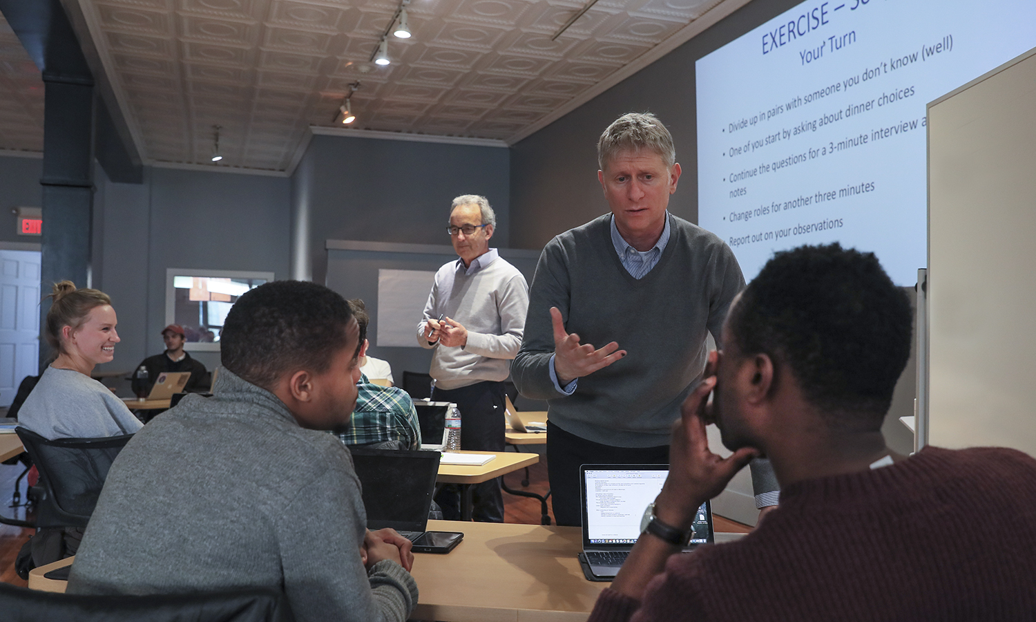 Professor of Economics Tom Drennen (left) and Margiloff Family Entrepreneurial Fellow Ed Bizari (right) work with students in the Bozzuto Center for Entrepreneurship.