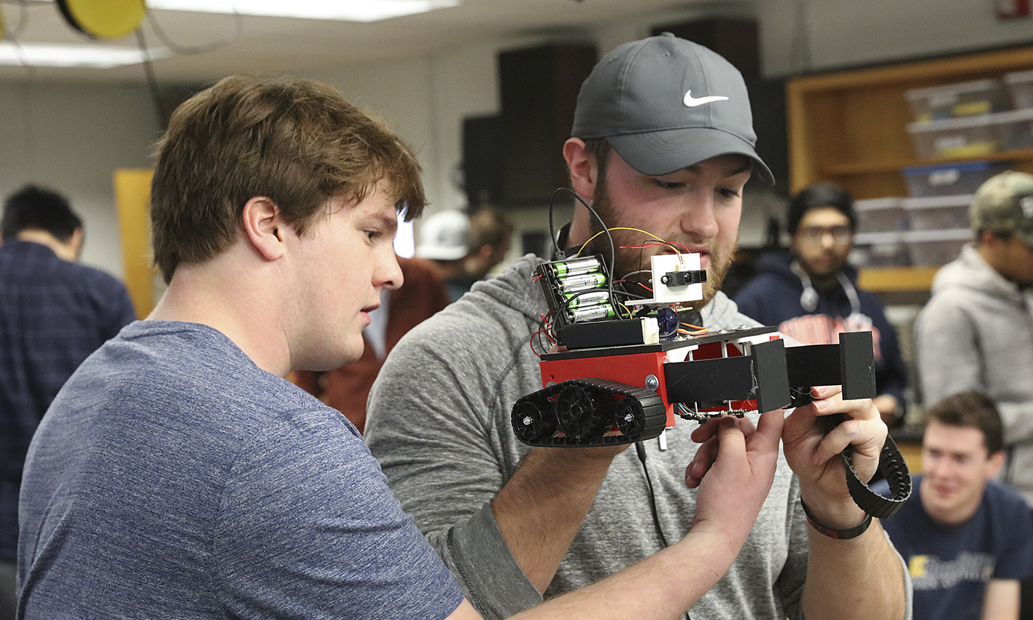 """Second photo shows Chase Brown on the left, and Jonathon Koch work on repairing an unexpected mechanical problem with their tractor tread robot named """"Wall-E""""."""