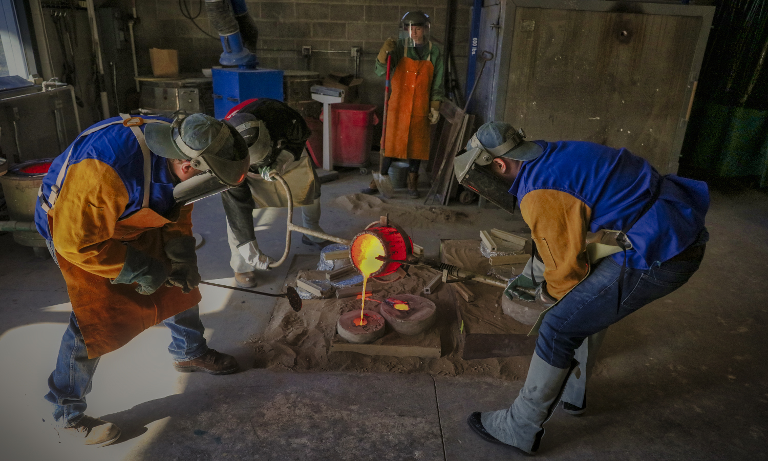 """Professor of Art and Architecture A.E. Ted Aub assists Bramm Watkin '20 and Zachary Birnbaum '16 as they pour bronze into a form as part of their """"Advanced Sculpture Workshop"""" class in the Katherine D. Elliott '66 Studio Arts Center."""