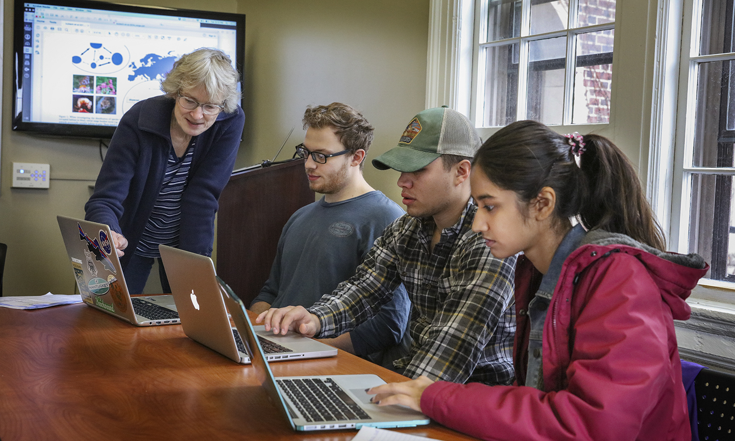 """Professor of Biology Beth Newell discusses species dispersal models in """"Biological Reponses to Climate Change"""" with Luke Pfund '18, Dan Robeson '18 and Shweta Patel '18 during a Biology senior seminar in Coxe Hall."""
