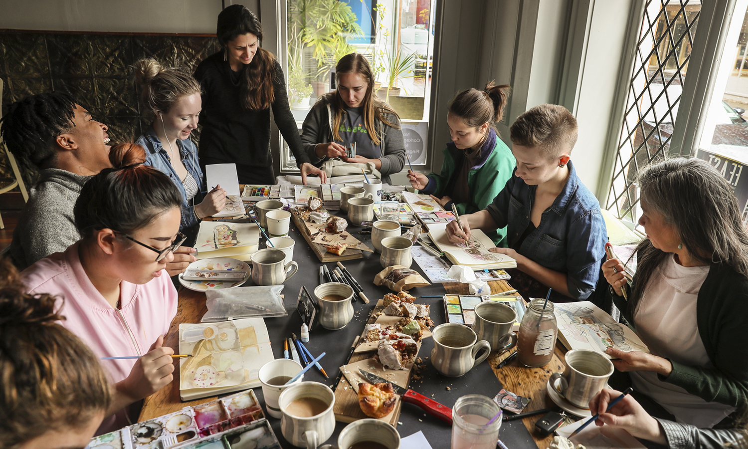 """Students paint gourmet donuts during their """"Watercolor Sketching"""" class with Associate Professor of Art and Architecture Kirin Makker at H.J. Stead Company on Linden Street in Geneva, N.Y."""